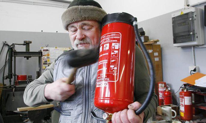 38b271a9b56 Tuletõrjeühingu töötaja Ants Kessler näitab, kuidas kustuti töökindlust  kontrollida: kopsa kummihaamriga ja siis kuulata, kas pulber kustutis  sahiseb.